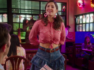 Janet with her hair in two ponytails. She's wearing a red and white checkered button down shirt, tied at the waist, and a blue jean skirt with large ruffles.