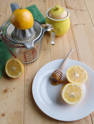 lemon half on juicer, lemons and honey pot
