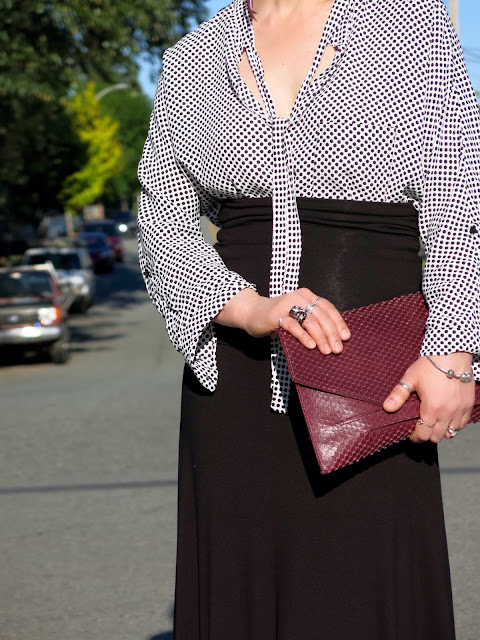 black maxi skirt, dotted blouse, reptile-embossed envelope clutch