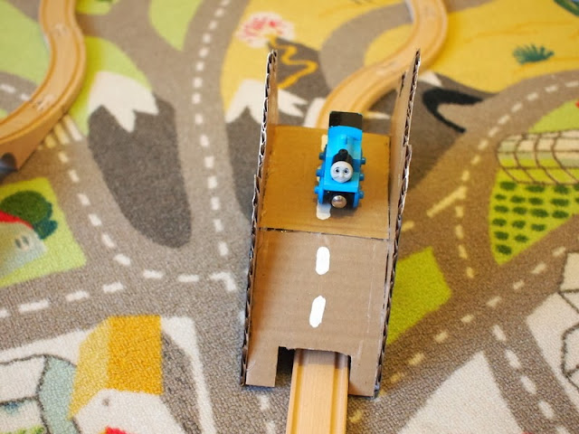 Train riding over DIY toy cardboard bridge
