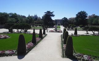 Vista general del jardín desde la cebecera. El monumento a J. Benavente en el cruce de amplios paseos bordeados de parterres y setos recortados.al con el