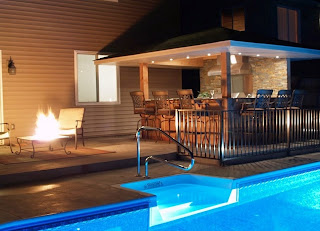 captivate backyard design with outdoor fire it near armchairs on black tile flooring plus white recessed lights in blue pool