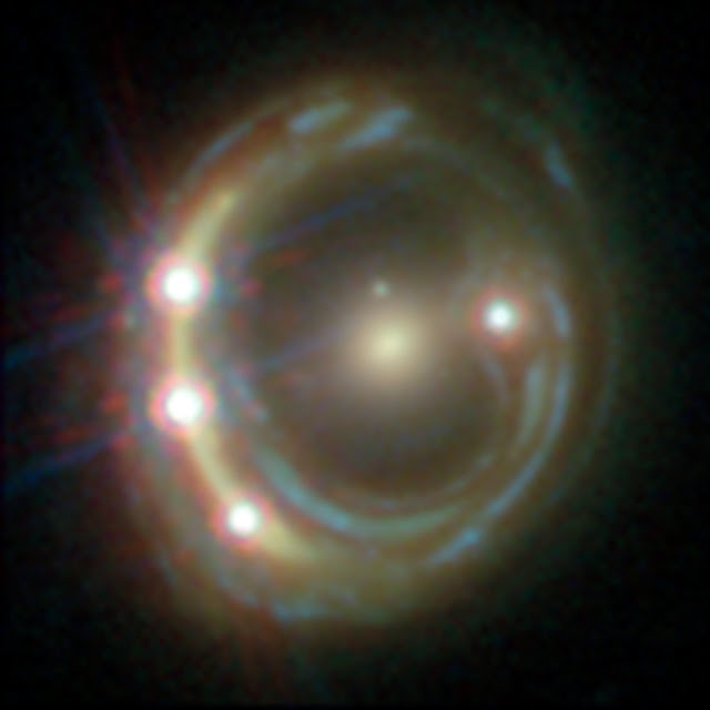 Hình ảnh quasar RXJ1131-1231 nằm ở xa bởi Kính Viễn vọng Không gian Hubble. Thiên hà nằm phía trước cùng với quasar nằm phía sau tạo nên cung sáng bên trái hình, hiện tượng này được gọi là thấu kính hấp dẫn. Thấu kính hấp dẫn cho phép các nhà khoa học đưa ra ước tính mới về tốc độ mở rộng của vũ trụ. Hình ảnh: ESA/Hubble, NASA, Suyu et al.