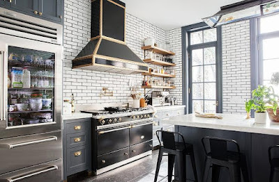 white swbuay tiles with grey grouts, blue cabinets and black LaChanche stove