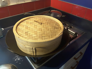 Large bamboo steamer, covered and sitting in wok on stove