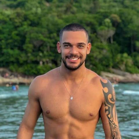 Ex-peão de 'A Fazenda', Caique Aguiar vai à praia de Guarujá e exibe abdômen sarado