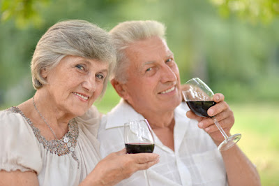 A happy elderly couple drinking wine.
