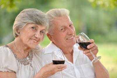 A happy elderly couple drinking wine.