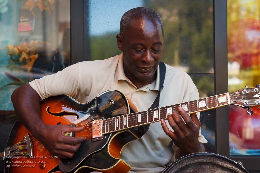 a candid photo of a jazz guitarist playing on the street in new york