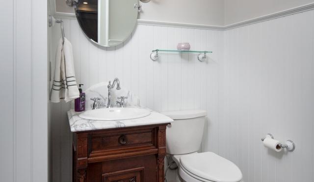Premier Surfaces Bathroom white walls and wood vanity