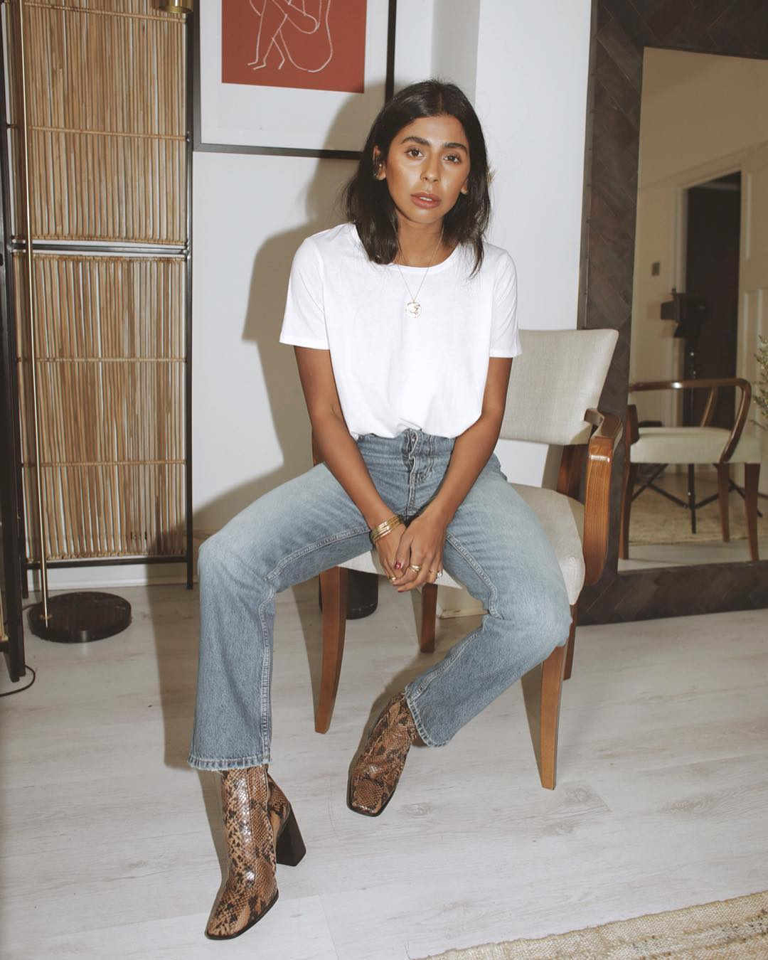 Spring Instagram Outfit Idea: Monikh Dale in a white t-shirt, straight-leg jeans, and snake-print ankle boots