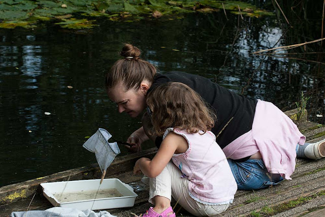 Girl pond dipping with her mum