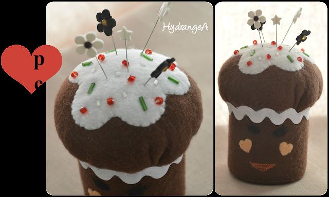 Alfiletero realizado en fieltro marrón y blanco, con forma de cupcake y decorado con rocalla y alfileres con forma de flor.