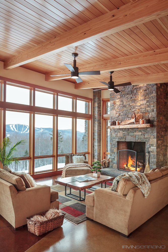 The living room, featuring a granite slab fireplace and a bird's eye maple mantel, utilizes floor to ceiling windows to accent the stunning view of Sunday River and the ski slopes.