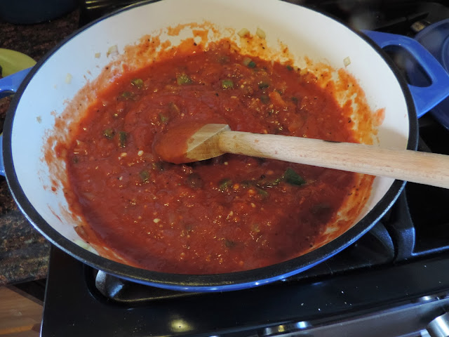 The crushed tomatoes being added to the pan.