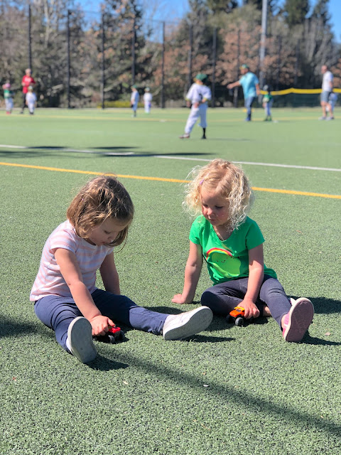 two girls sitting on a turf field playing with toy cars
