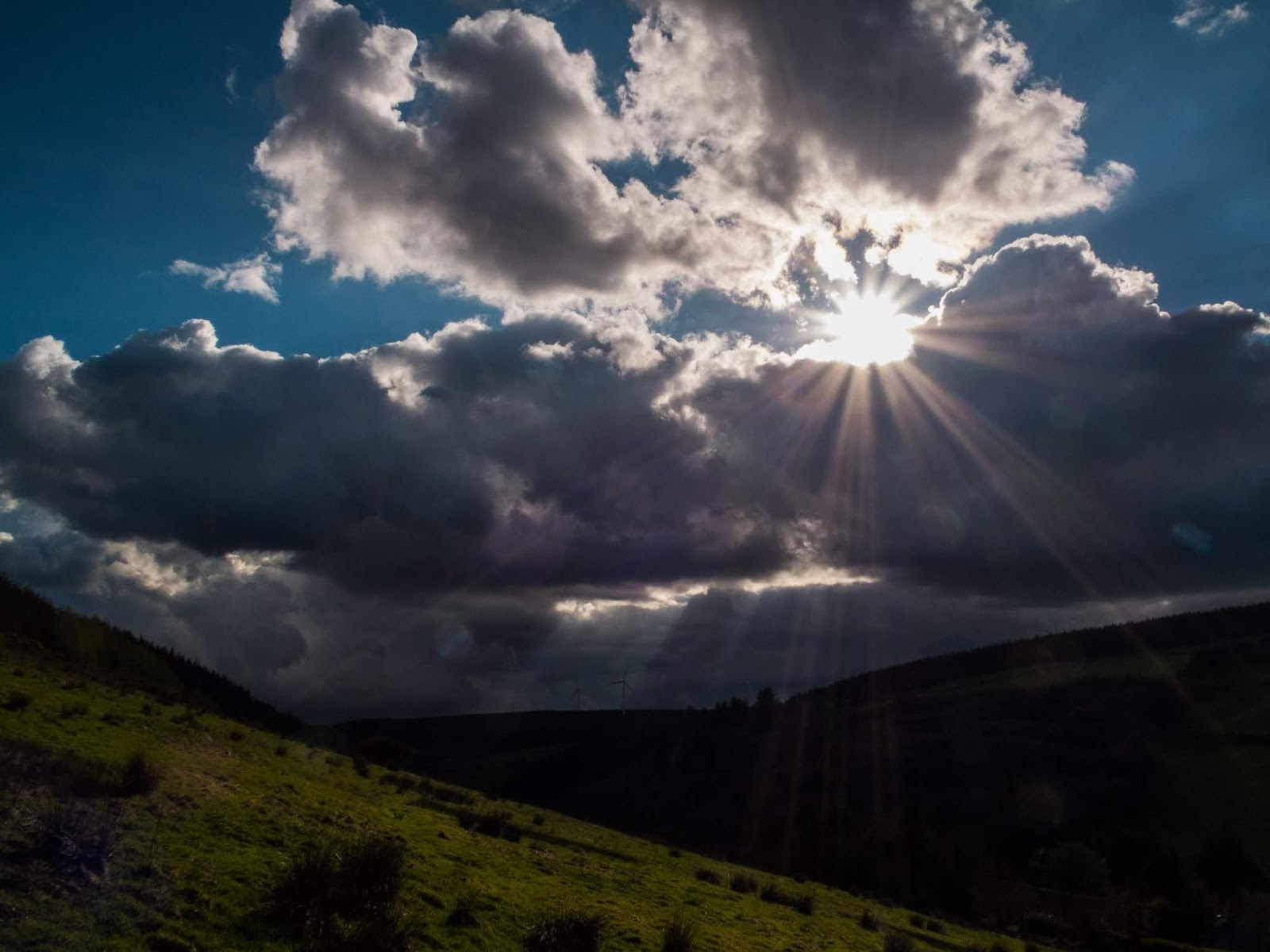 Sun shining with rays coming through clouds over a valley in Co.Cork, Ireland.