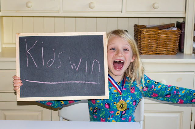 "A happy child holding a blackboard saying ""Kids Win"" and wearing a winners medal"
