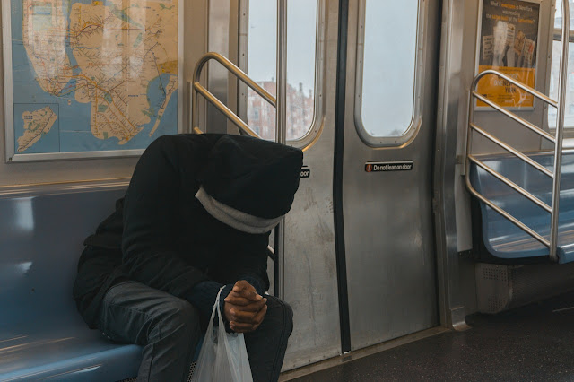 Man looking defeated on subway, gloomy