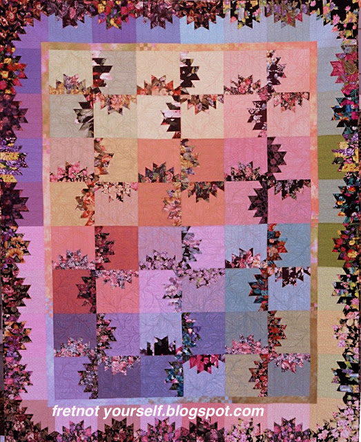 Scrap quilt using black background florals and solid pastels.