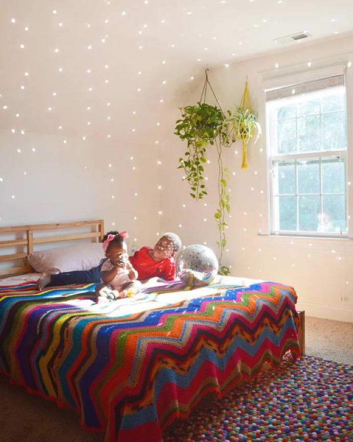 Disco ball on thrifted afghan with #plants in bedroom- design addict mom
