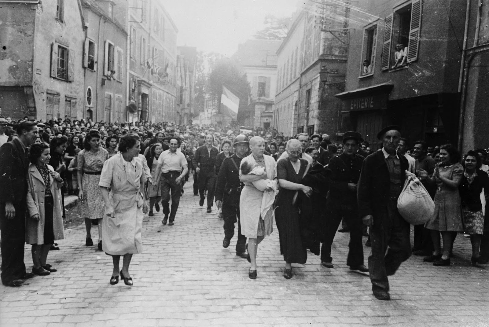 A woman, with her baby whose father is German, and her mother are jeered and humiliated by crowds in Chartres after having their heads shaved as punishment for collaborating with the German troops.