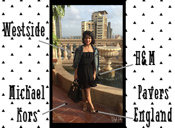 Image of female indian fashion blogger wearing a little black dress, gold shoes and denim jacket and black satchel bag