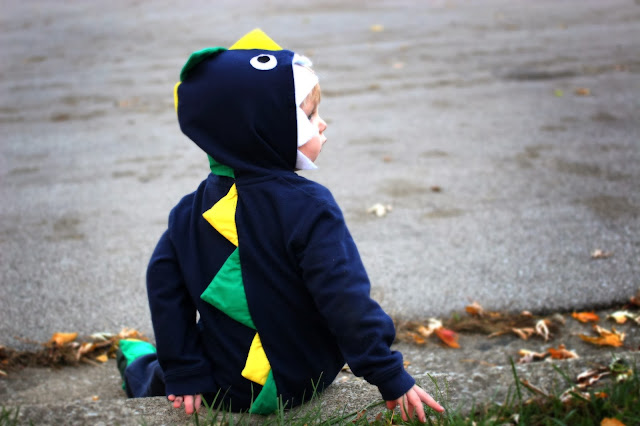 Little boy sitting down while wearing a DIY dinosaur costume