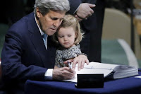 U.S. Secretary of State John Kerry holds his two-year-old granddaughter Isabelle Dobbs-Higginson as he signs the Paris Agreement on climate change at United Nations Headquarters in Manhattan, New York, U.S., April 22, 2016. (Credit: Reuters/Carlo Allegri) Click to Enlarge.