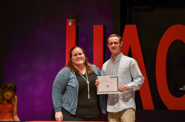 woman and man on stage, holding a certificate