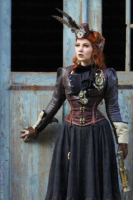Steampunk redhead dressed as a huntress. Gun, skirt, underbust corset, bolero jacket, top hat fascinator and fingerless gloves. Women's steampunk fashion and clothing inspiraton.
