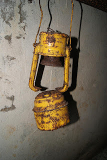 Eine alte, gelbe und zum Teil verrostete Petroleumlampe hängt an der Decke