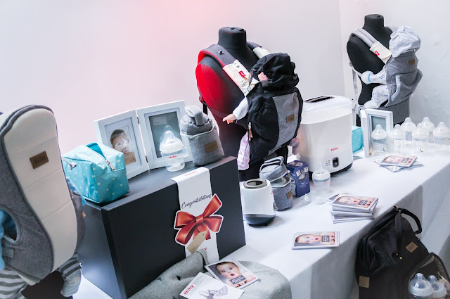 baby carriers, bottles, changing bags and gift sets on display against white background at nuby big reveal event