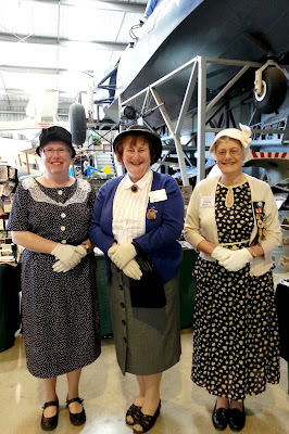 Three women dressed in 1940s outfits in front of a stall at a miniatures convention.