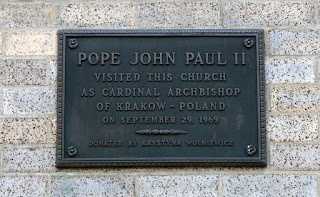 Exterior bronze plaque commemorating Pope John Paul the Second's visit as a Cardinal in 1969