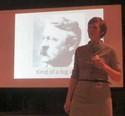 Maggie Koerth-Baker standing in front of a projected image of a 19th century old white man with a big mustache