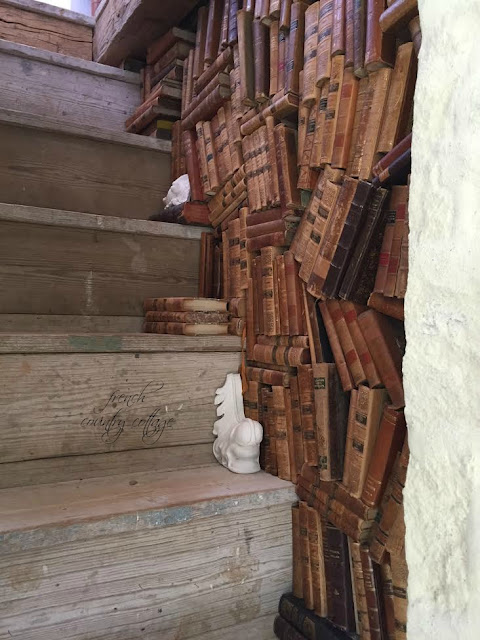Stack of old books on wall and stairway