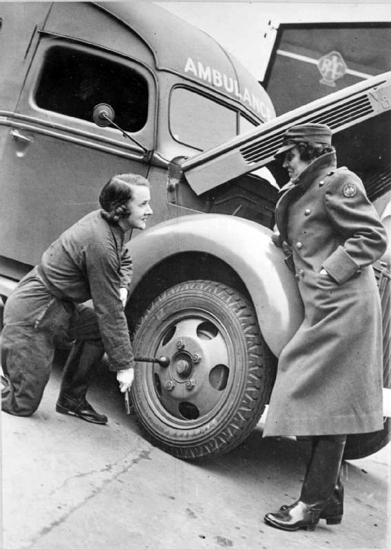 Women of the MTC - Mrs Pat Macleod tightens a nut on the wheel of her ambulance as Miss Winifred Ashford looks on. The bonnet of the ambulance is open, ready for an inspection of the engine to be carried out. This photograph was probably taken at the depot in Paddington in 1940
