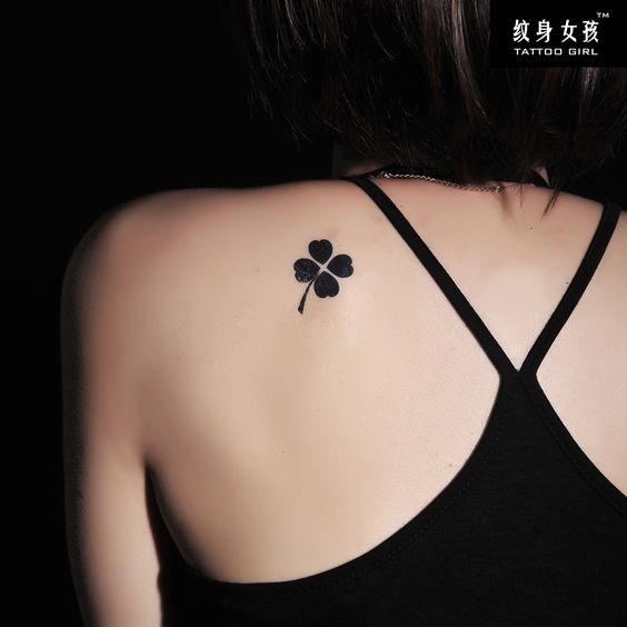 chica morena de espaldas, lleva un tatuaje de trebol en el omoplato.