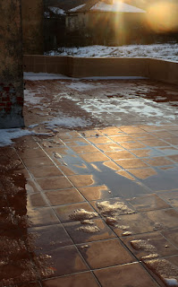 Sunset reflected on ice and water on the balcony