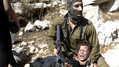 Soldado israelí detiene a un niño palestino durante una protesta en la ocupada Cisjordania.