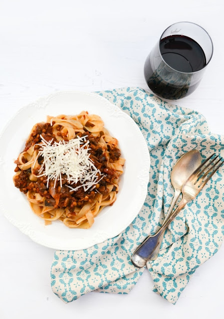 A bowl of Rich Mushroom and Lentil Ragu on tagliatelle with a glas of red wine
