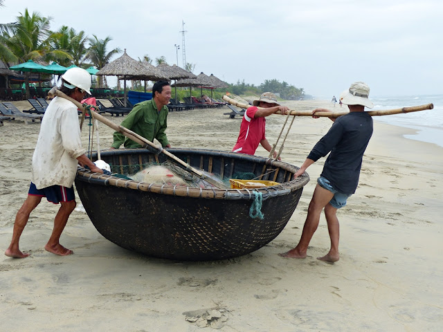 Vietnamese fishermen ready to sail on their hemispherical boat, Hoi An