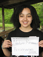 Youth holds sign reading Nature Resources Preservation