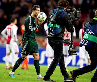 Cristiano Ronaldo kisses a ball wiearing the Real Madrid green jersey