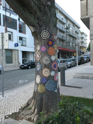 Tree in public space covered in crochet squares and laces