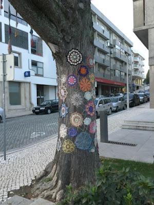 Yarn bombing d'un arbre dans un espace public a Feira au Portugal