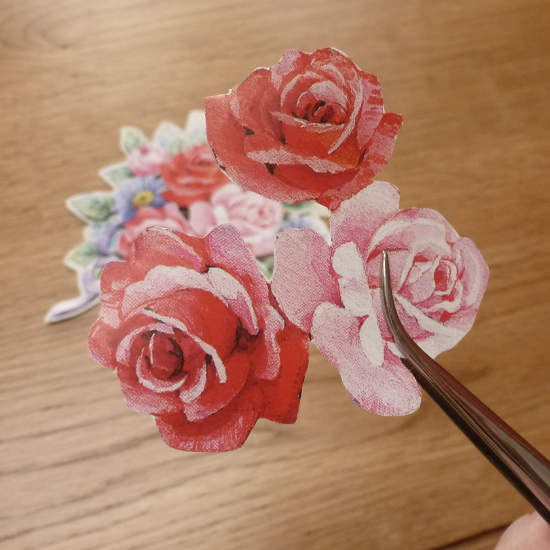Rose flower printed paper pattern cut out and held up with craft tweezers