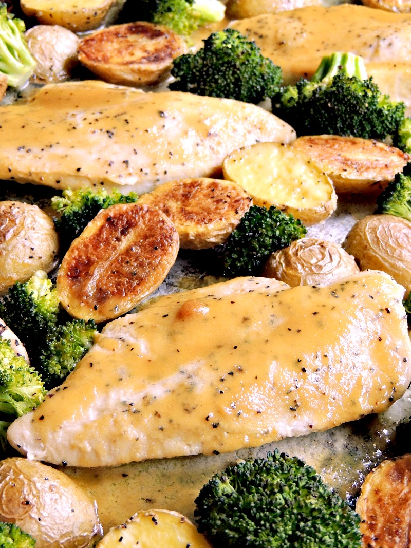 Close up of honey mustard chicken with broccoli and potatoes on a sheet pan.