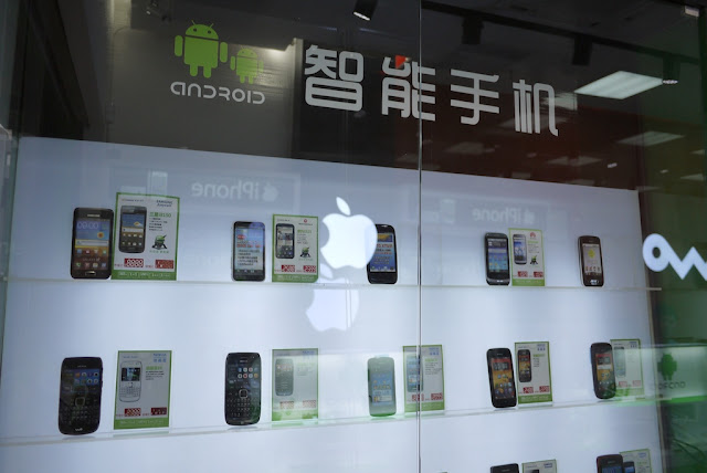 Android display case of a variety of phones reflecting the Apple logo in the Android Store in Nanping, Zhuhai, China